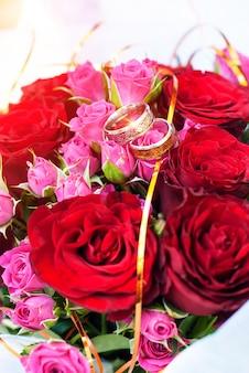 Alianças de casamento em um buquê de casamento com rosas cor de rosa e vermelhas