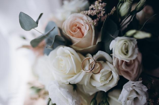 Alianças de casamento em um buquê de flores brancas e rosa.