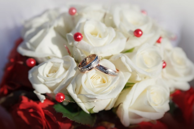 Alianças de casamento em um buquê de rosas bege