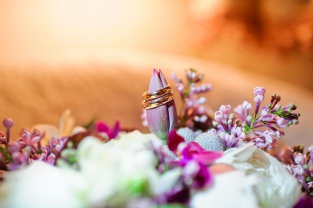 Alianças de casamento em um fundo de flores, fim do ouro acima.