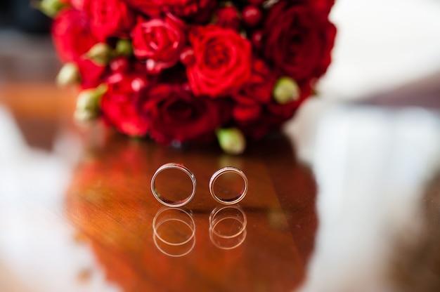 Alianças de casamento em um fundo de rosas vermelhas.