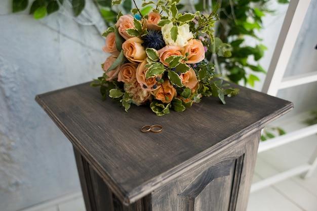 Alianças de casamento em um pedestal de madeira matizada no fundo de um buquê de casamento elegante