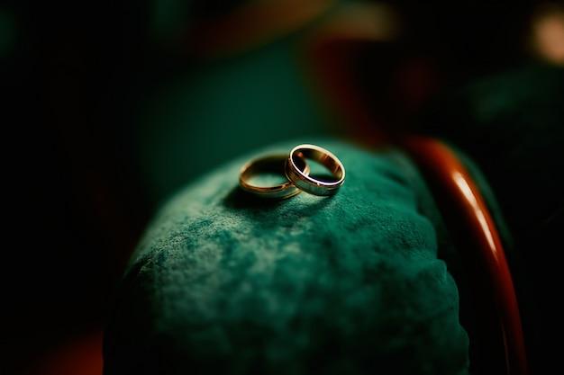 Alianças de casamento em um veludo verde.