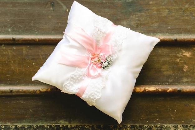 Alianças de casamento em uma almofada branca.