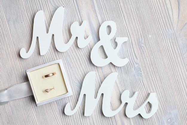 Alianças de casamento em uma caixa ao lado das inscrições sr. e sra. em uma mesa de madeira.