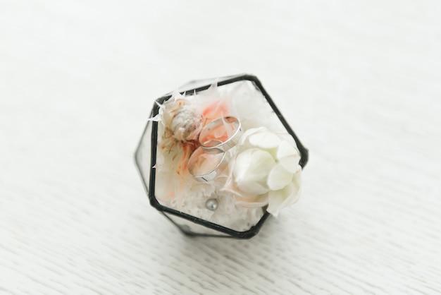 Alianças de casamento em uma caixa com flores, decoração e detalhes da cerimônia de casamento, foco seletivo, macro