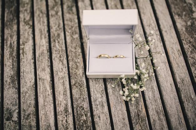 Alianças de casamento em uma caixa em cima da mesa. pequenas flores em uma mesa de madeira