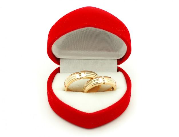 Alianças de casamento em uma caixa vermelha em forma de coração