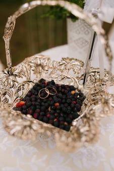 Alianças de casamento em uma cesta com frutas - mirtilos, na frente de uma gravação de campo dos noivos, casamento rústico, foco seletivo