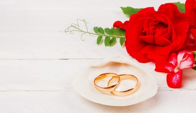 Alianças de casamento em uma concha do mar branca e flores de rosas vermelhas em um fundo branco de madeira com espaço de cópia