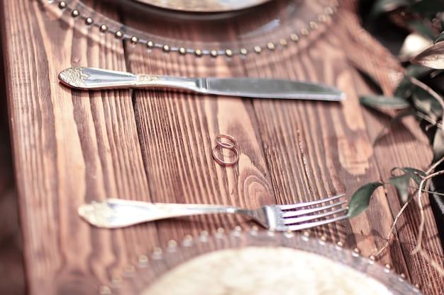 Alianças de casamento em uma mesa de madeira na floresta