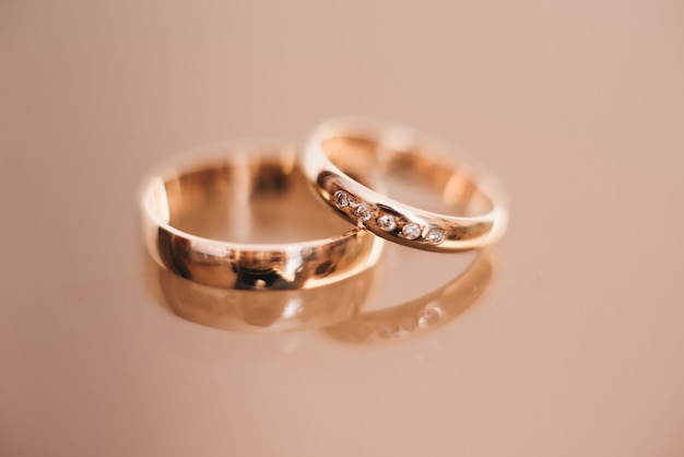 Alianças de casamento em uma superfície clara, foco seletivo, macro