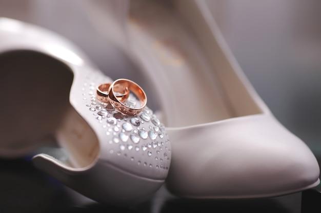 Alianças de casamento fecham nos sapatos da noiva.