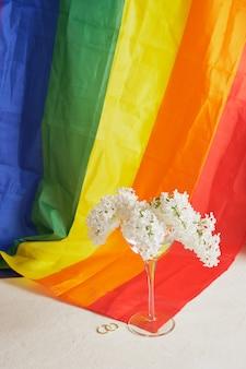 Alianças de casamento, fita do arco-íris lgbt e um buquê de lilases. símbolo da fita de orgulho. copie o espaço. conceito de direitos lgbt.