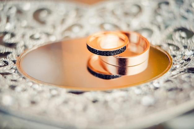 Alianças de casamento. jóias em ouro branco e amarelo. aliança na superfície do espelho.