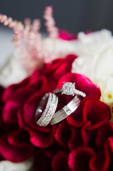 Alianças de casamento luxuosas com diamantes em um fundo das flores, fim acima.