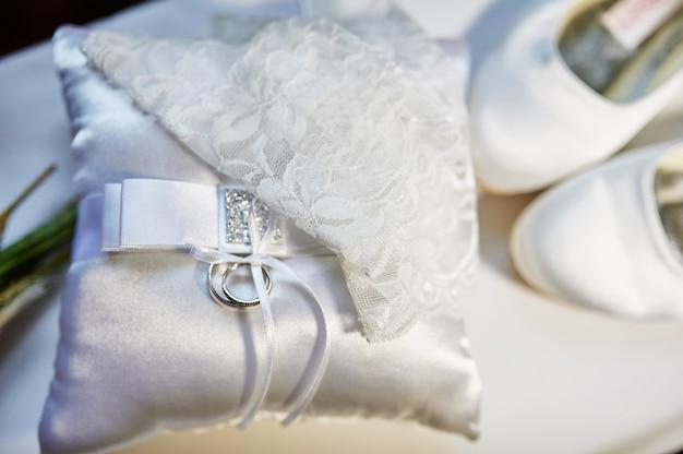 Alianças de casamento na almofada e sapatos brancos da noiva