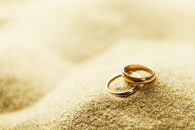 Alianças de casamento na areia