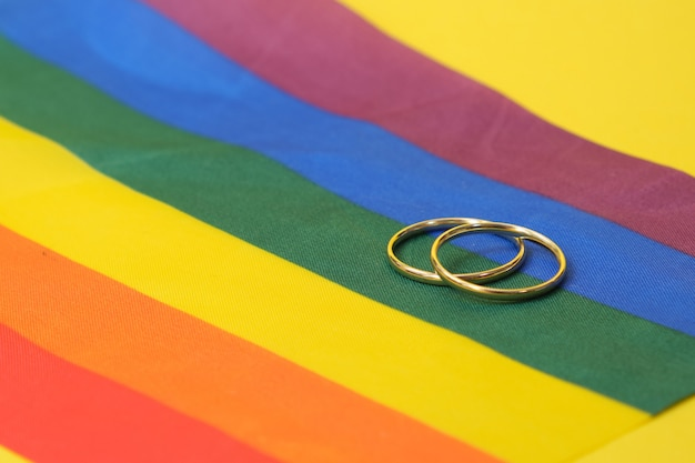 Alianças de casamento na bandeira lgbt, fundo amarelo, espaço de cópia