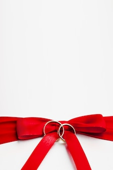 Alianças de casamento na curva vermelha no fundo de seda branco.