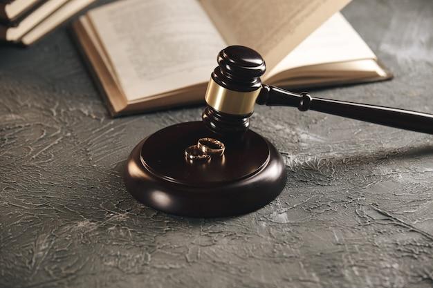 Alianças de casamento na figura de um coração partido de uma árvore, o martelo de um juiz em um fundo de madeira. divórcio processo de divórcio