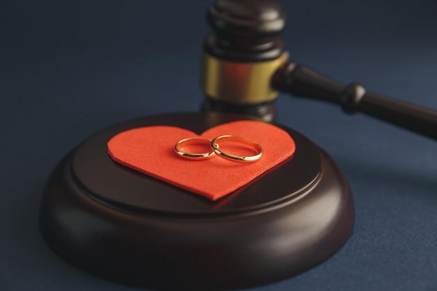 Alianças de casamento na figura de um coração partido de uma árvore, o martelo de um juiz em um fundo de madeira. processo de divórcio
