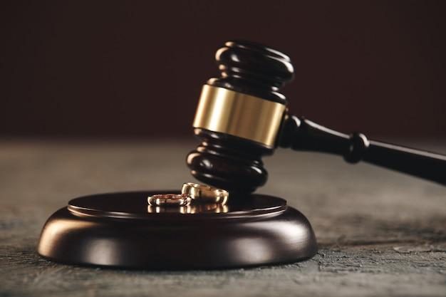 Alianças de casamento na figura de um coração partido de uma árvore, o martelo de um juiz em um fundo de madeira. processo de divórcio.