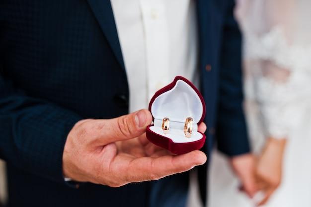 Alianças de casamento na mão do noivo na caixa em forma de coração