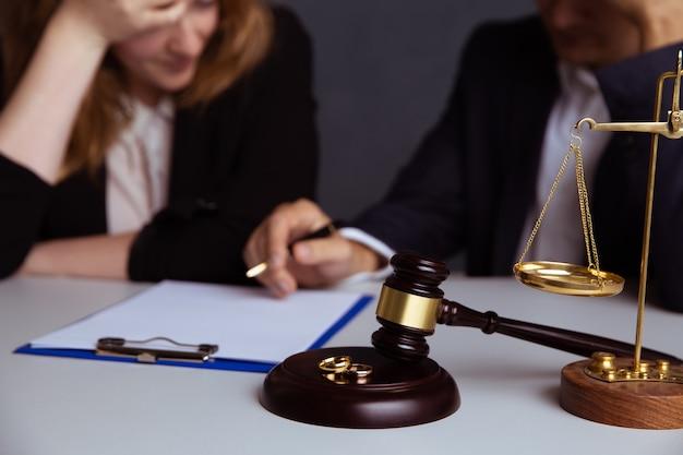 Alianças de casamento na placa de madeira e martelo do juiz com casal se divorciando