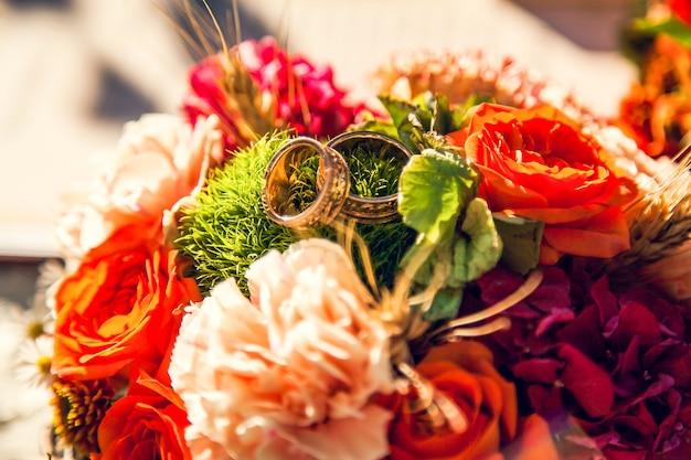 Alianças de casamento no buquê da noiva no tema outono.