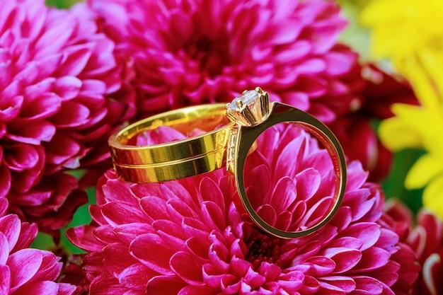 Alianças de casamento no buquê de flores cor de rosa