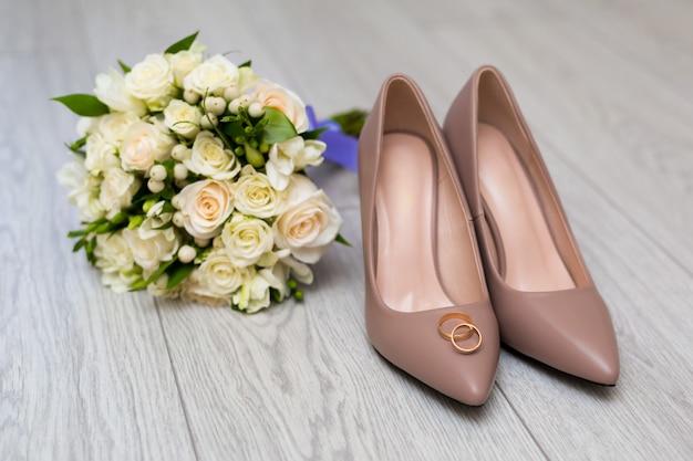 Alianças de casamento nos sapatos da noiva.