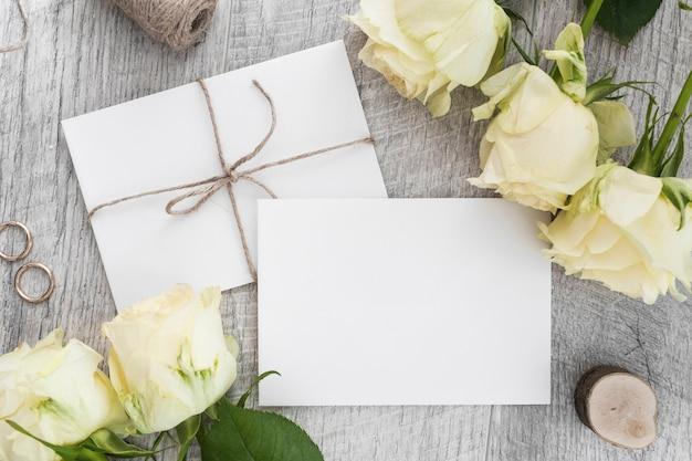 Alianças de casamento; rosas e dois envelopes brancos em pano de fundo de madeira