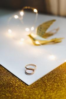 Alianças de casamento sobre fundo dourado com enfeites.