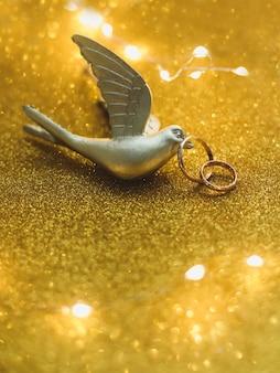 Alianças de casamento sobre fundo dourado com pássaro de brinquedo e decorações.