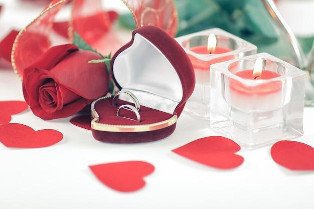 Alianças de casamento, velas e rosa