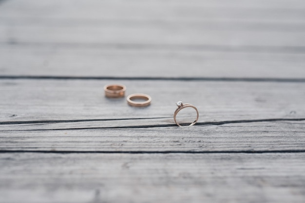 Alianças de noiva e do noivo no fundo de madeira