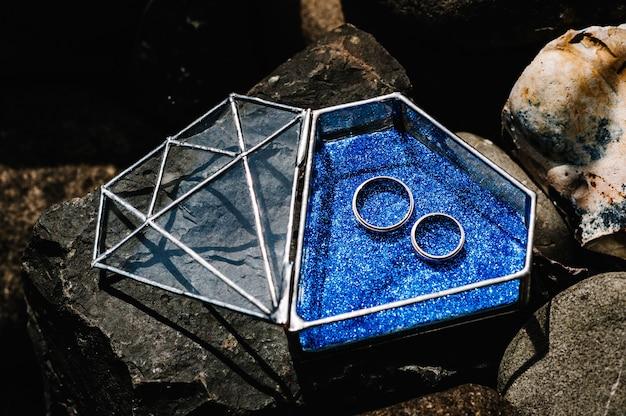 Alianças de noivado de prata dourada em uma superfície azul brilhante.