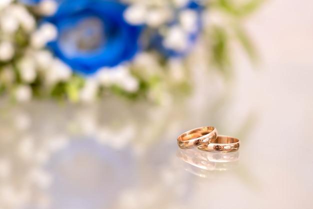 Alianças de ouro ao lado do buquê de rosas azuis da noiva em uma superfície de vidro com reflexo