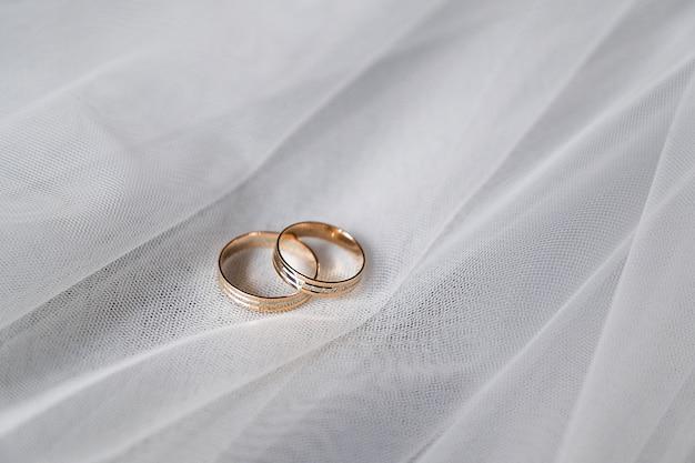 Alianças de ouro com pedras preciosas no véu da noiva.