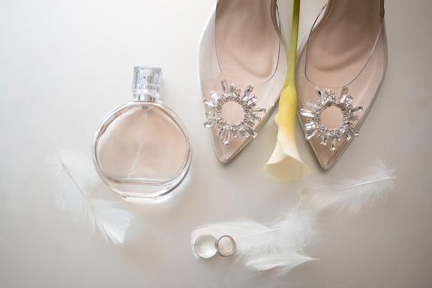 Alianças de ouro com penas ao lado dos sapatos bege da noiva decorados com pedras nas quais está uma flor amarela e ao lado de um frasco de perfume chanel