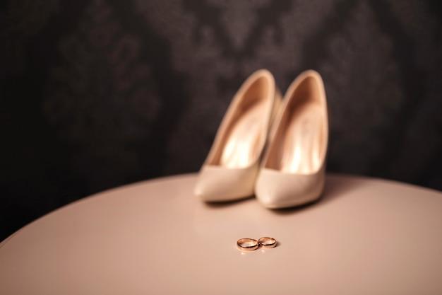 Alianças de ouro e sapatos femininos da noiva da noiva. noivado. detalhes de decoração de casamento itens noivos na mesa branca. dia da noiva