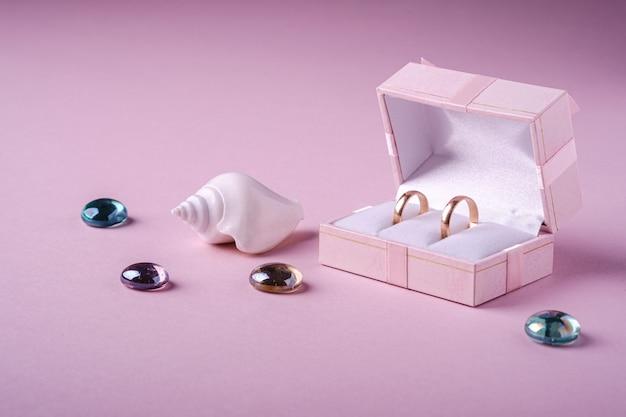 Alianças de ouro em caixa de presente rosa com conchas do mar brancas e bolinhas de vidro no fundo rosa suave, vista de ângulo, cópia espaço