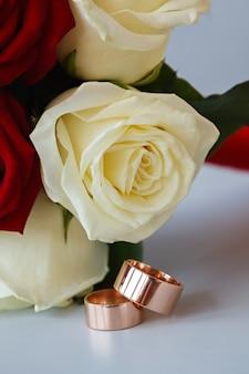 Alianças de ouro em um buquê de flores para a noiva