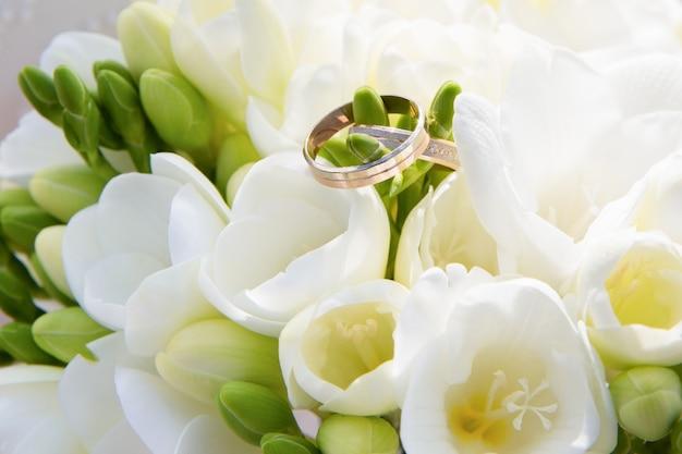 Alianças de ouro em um buquê de flores