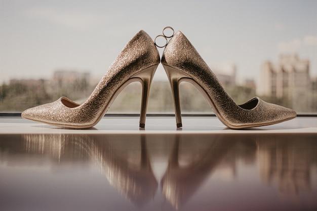 Alianças de ouro entre um par de sapato de salto alto dourado