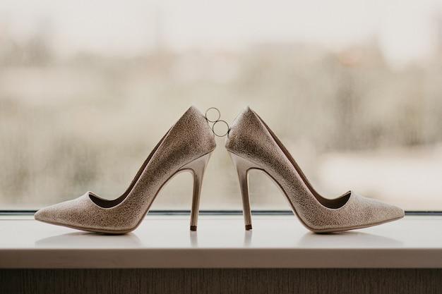 Alianças de ouro entre um par de sapatos de salto alto dourados