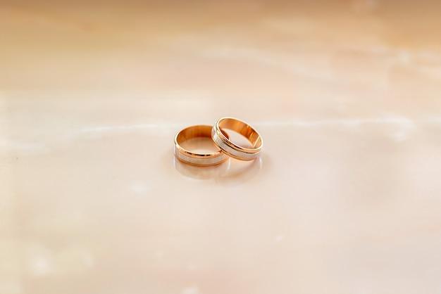Alianças de ouro na parede de mármore. se casou noivado.