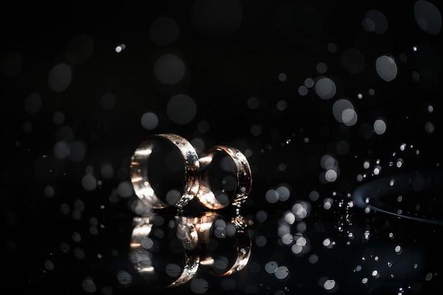 Alianças de ouro para recém-casados em um dia de casamento em um fundo preto com gotas de água. joalheria