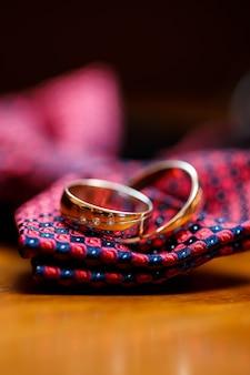 Alianças de ouro penduradas na gravata-borboleta de um homem